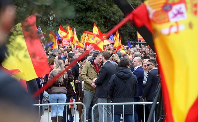 Asistentes a la concentración en la Plaza de Colón en Madrid bajo el lema 'Por una España unida' enarbolan banderas españolas.