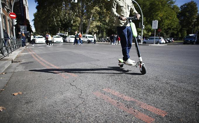 Un patinete pasa cerca de una línea naranja que indica restricción al tráfico en el centro de Madrid