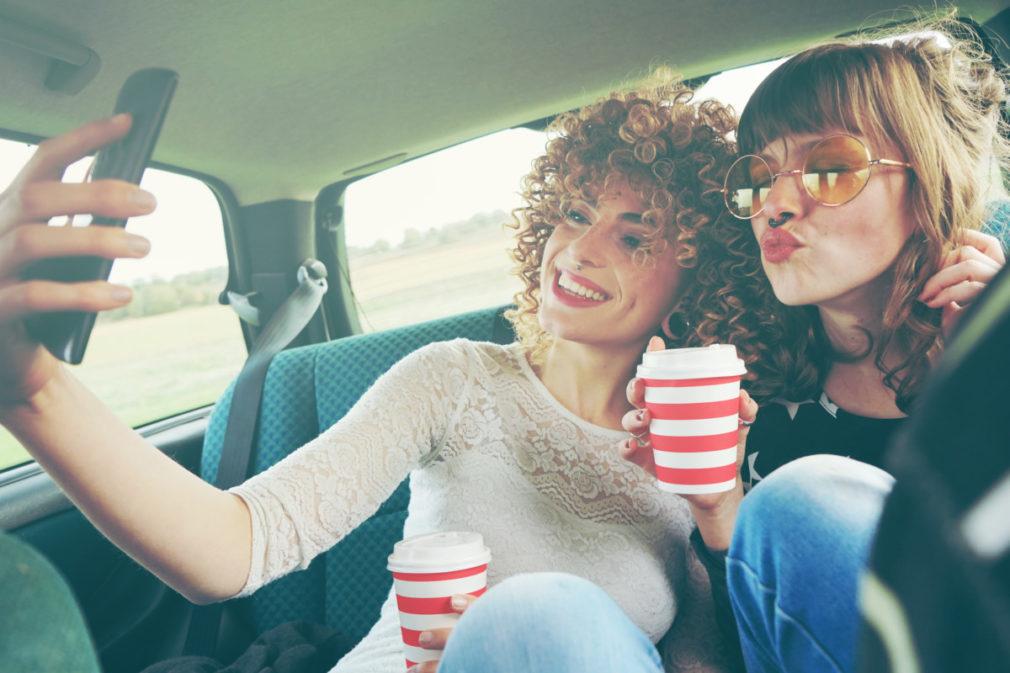 Dos chicas viajando juntas y haciéndose fotos con su teléfono móvil