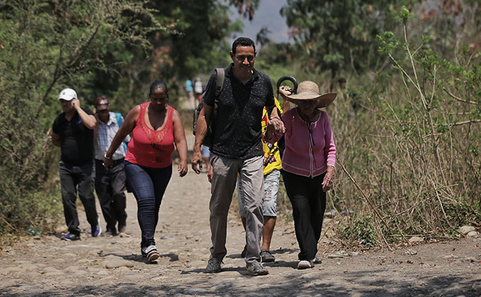 25 February 2019, Colombia, Cucuta: Venezuelans walk through unofficial rout on their way to Colombia after it closed all border crossings with Venezuela for 48 hours because of the damage had been caused by the clashes between demonstrators and Venezuela