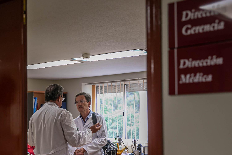 El portavoz del gabinete técnico creado por la Consejería de Salud y Familias para el seguimiento del brote de listeriosis, José Miguel Cisneros (d) conversa con un colega al finalizar la rueda de prensa ofrecida para informar sobre el brote y los nuev