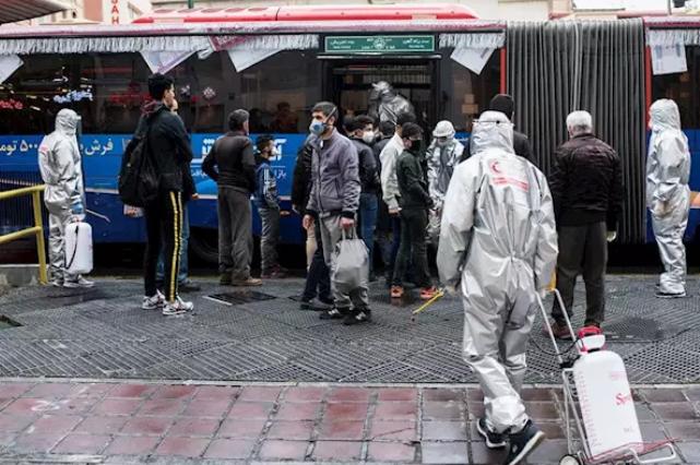 Trabajadores voluntarios desinfectando un autobús en Teherán - Arash Khamooshi
