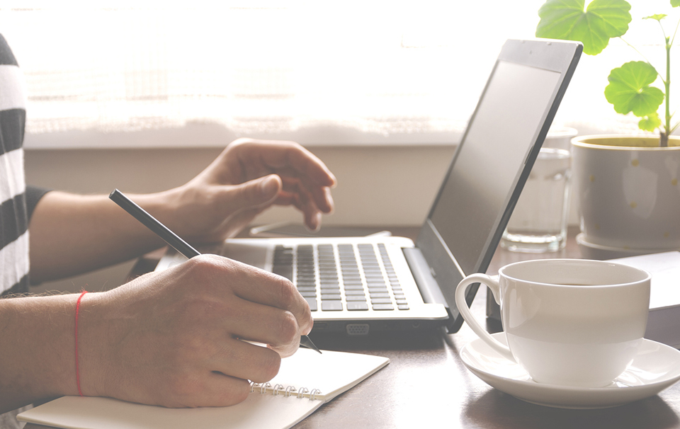 Freelancer works in the home office sitting at the desk near the window