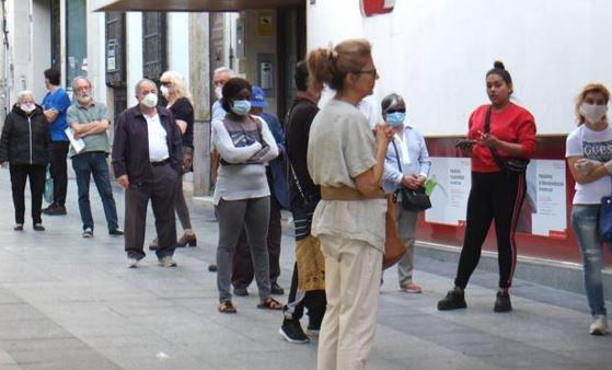 Personas esperan en la cola de un banco.