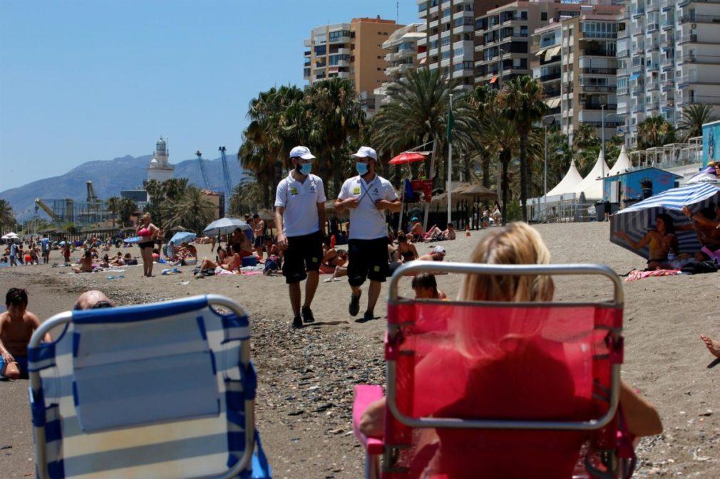 Una pareja de Vigilantes de la playa de Andalucía asesoran a bañistas sobre las medidas preventivas