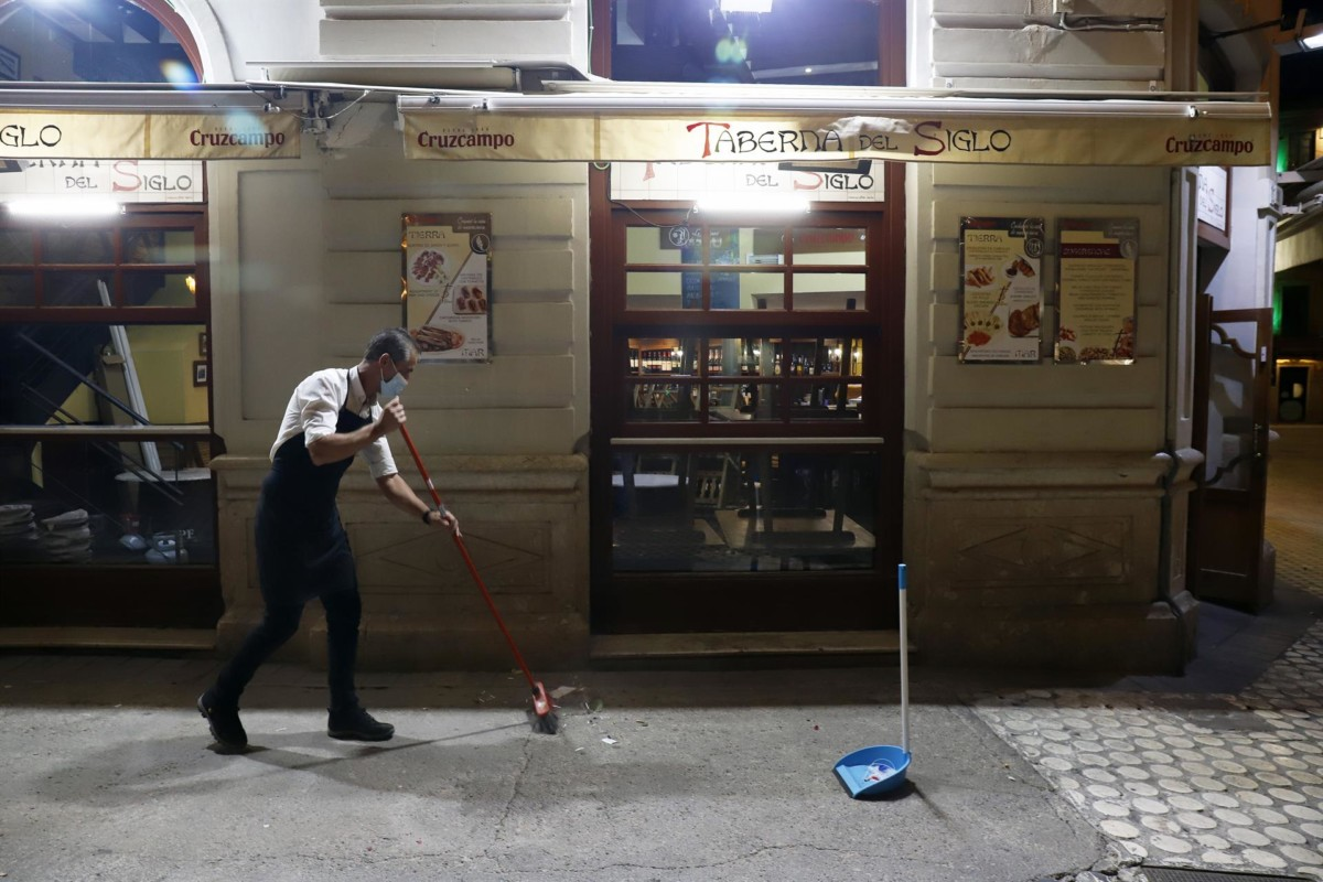 Dos camareros se afanan en recoger la terraza de un bar ubicado en el centro de Málaga – Álex Zea – Europa Press