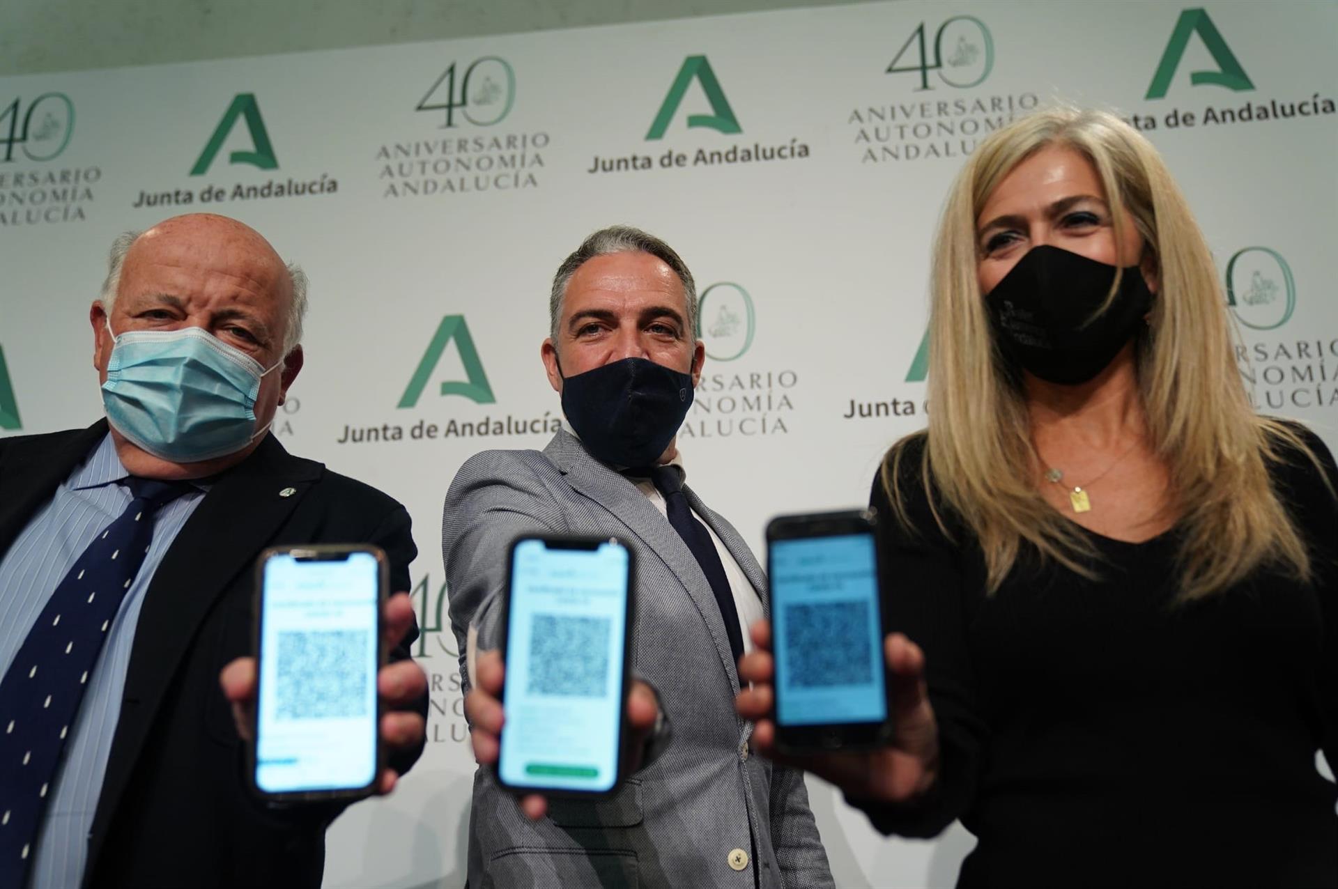 Los consejeros Jesús Aguirre (i.), Elías Bendodo (c.) y Patricia del Pozo, este martes, mostrando el acceso al código QR