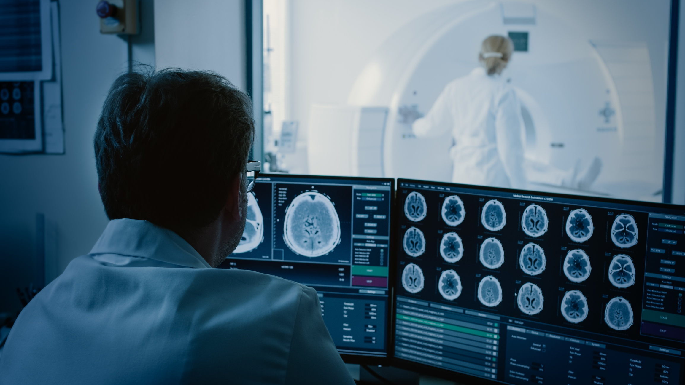 In Medical Laboratory Patient Undergoes MRI or CT Scan Process under Supervision of Radiologist, in Control Room Doctor Watches Procedure and Monitors with Brain Scans Results.