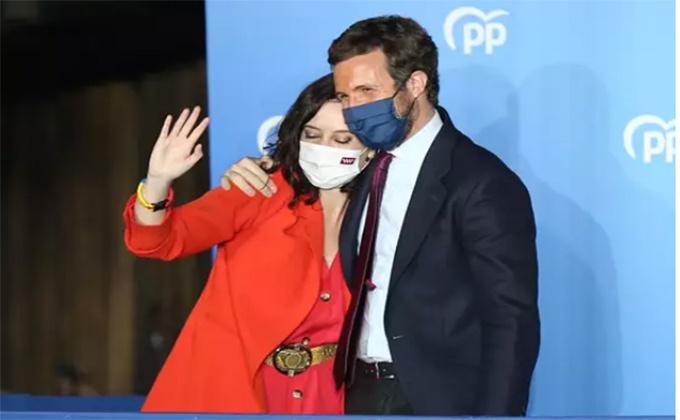 La presidenta de la Comunidad de Madrid y candidata a la reelección por el PP, Isabel Díaz Ayuso; y el líder del PP, Pablo Casado, saludan para celebrar la victoria - Cézaro De Luca - Europa Press