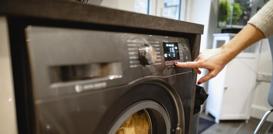 Una persona programando una lavadora istock
